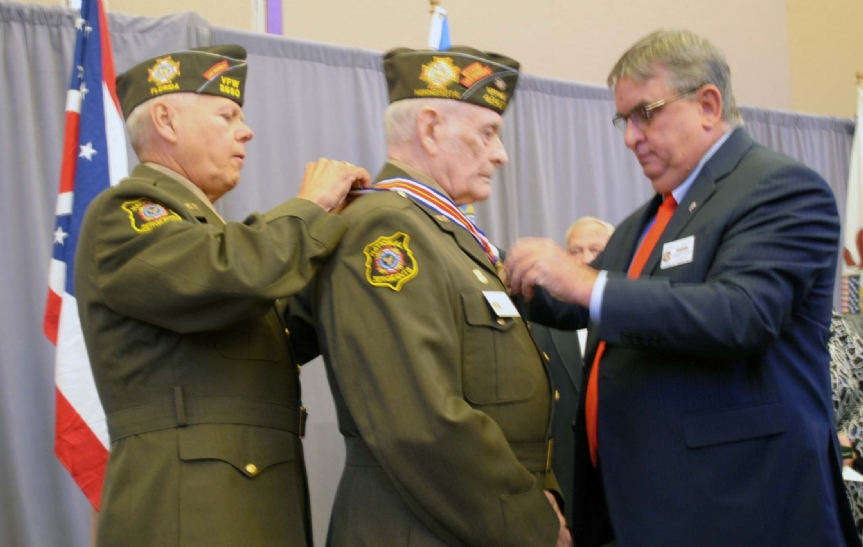 NCIC Brian Duffy places a Gold Medal around the neck of Joseph Schirmers for his long service to the honor guard