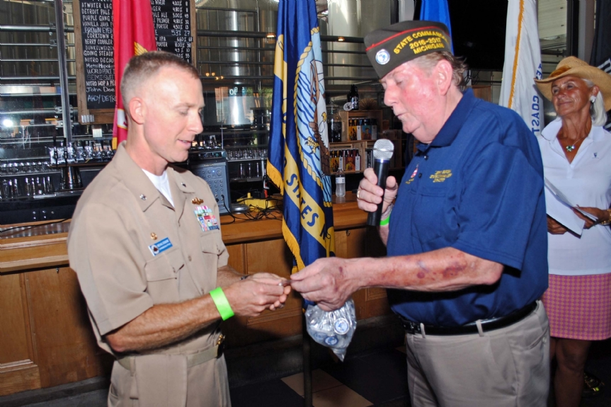 Commander Gorski giving Commander Desmond a challenge coin