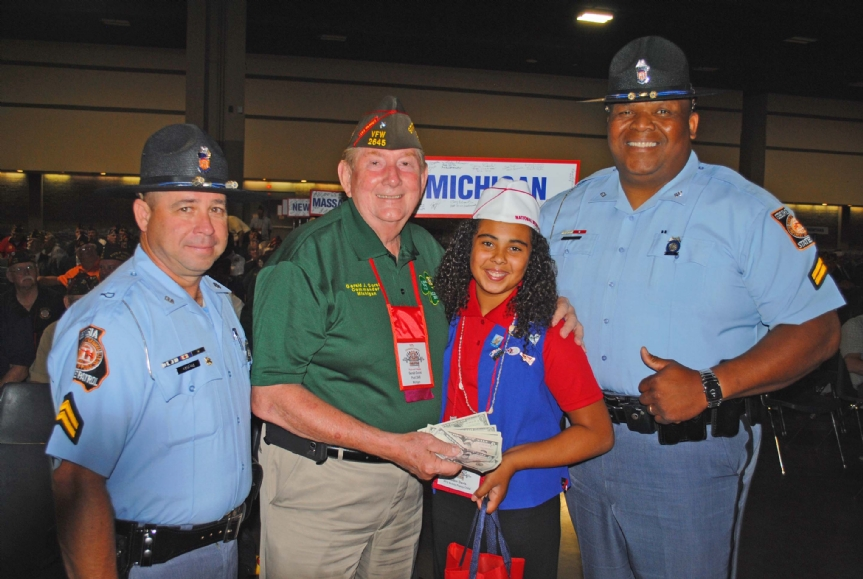 Department of Michigan presenting donation to Buddy Poppy Child along with a very large State Trooper as bodyguard